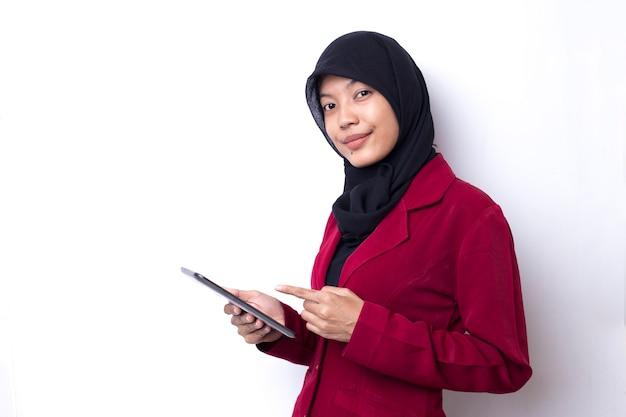 Красивая азиатская женщина студента с портретом хиджаба используя телефон на пустом пространстве