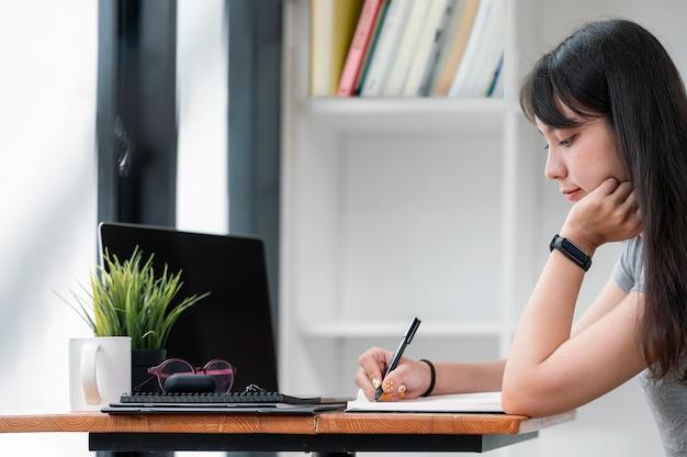Красивый азиатский студент писать на ноутбуке и использовать портативный компьютер для онлайн-обучения белый оставаясь дома.