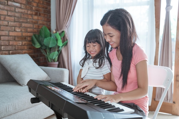 Beautiful asian teen girl playing a piano instrument
