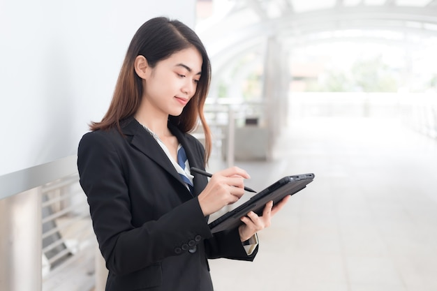 Beautiful asian thai businesswoman using a tablet to take notes.