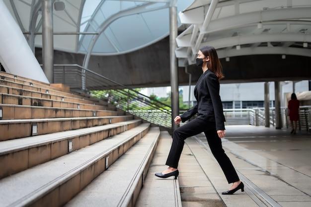 Красивая азиатская тайская бизнесвумен в черном костюме поднимается по лестнице на работу в бангкоке, таиланд.