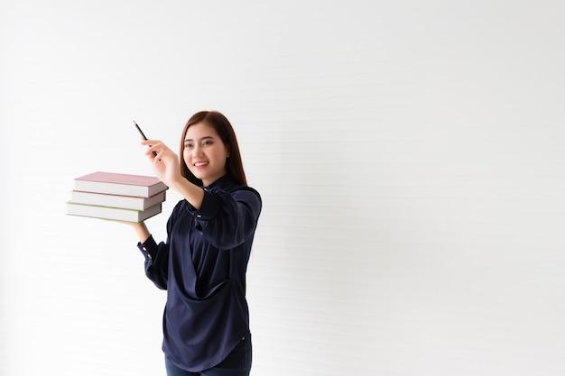 美しいアジアのタイ人女性彼女は紺色のドレスを着て、たくさんの本を持って、まるでそれを書いて見ようとしているかのようにペンを持っていました。白い壁を背景に