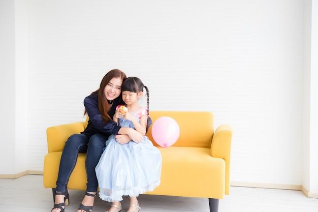 아름다운 아시아 태국 여성 남색 평상복을 입고 노란색 소파에 앉아 미소와 행복으로 한 소녀를 껴안고 있었습니다.