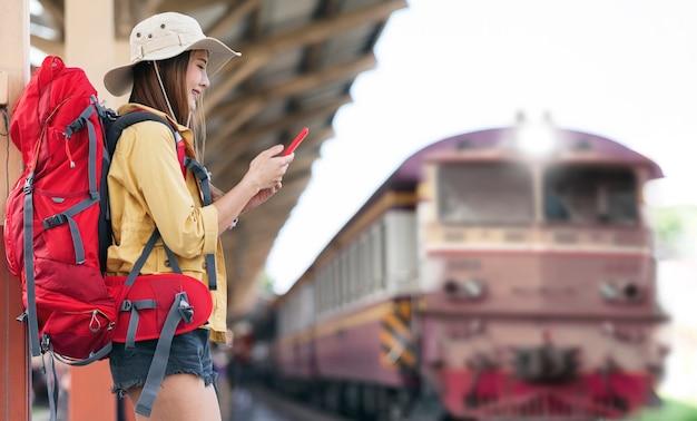 駅に立って出発を待っている間、スマートフォンを使ってバックパックを背負った美しいアジア人旅行者