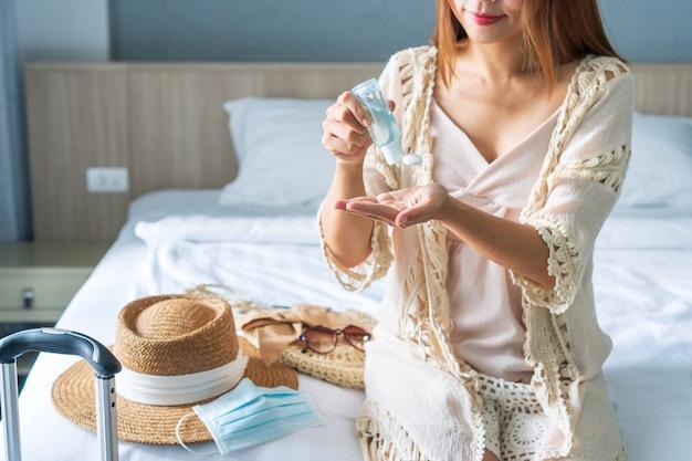 아름 다운 아시아 여행자 여자 침대에 앉아 그녀의 손에 소독 젤을 적용합니다.