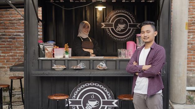 Красивая азиатская официантка и крутой красивый парень у контейнерной будки ангкрингана