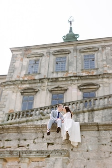 Beautiful asian wedding couple poses while sitting on the stone wall of an old ruined castle