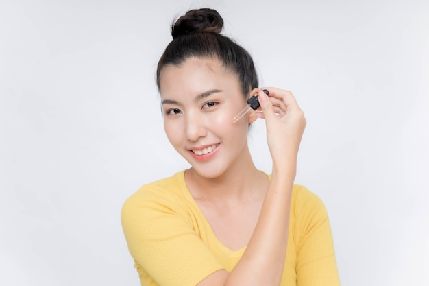 그녀의 얼굴에 노화 방지 보습 세럼을 적용하는 아름 다운 아시아 여자