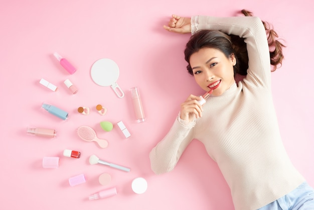 Beautiful asian woman applying lipstick while she lying on pink