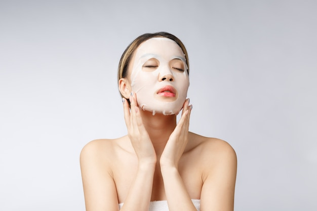 Beautiful asian woman applying paper sheet mask on her face white background