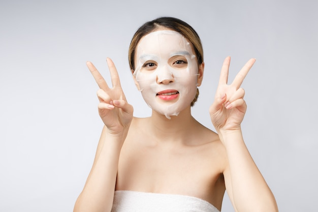 Beautiful asian woman applying paper sheet mask on her face white background.