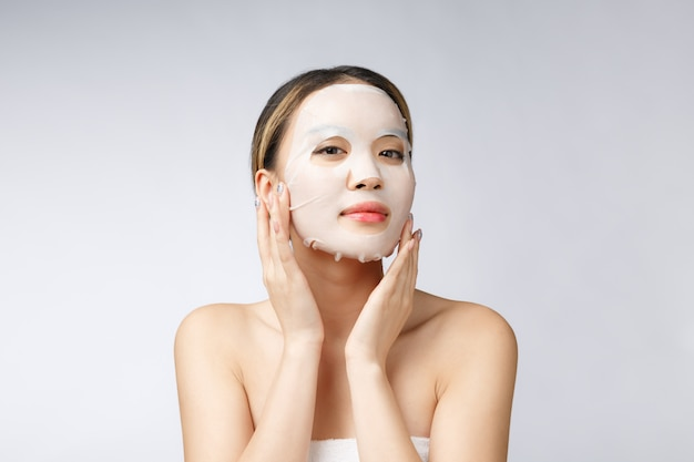 Красивая азиатская женщина прикладывая маску листа бумаги на ее предпосылке белизны стороны