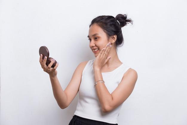흰색 배경에 격리된 화장품 화장에 파우더를 바르는 아름다운 아시아 여성