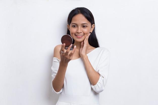 白い背景で隔離の化粧品のメイクアップでパウダーを適用する美しいアジアの女性