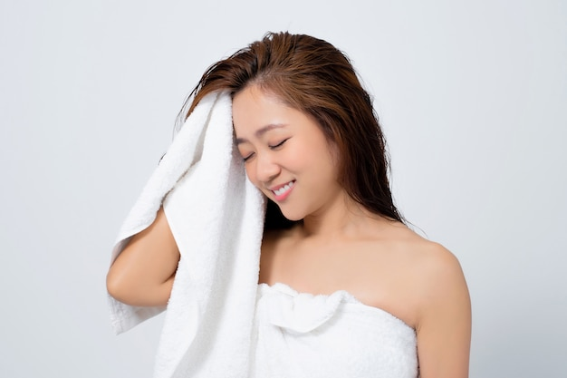Beautiful asian woman are happy to use dry towels to dry their hair on a white background in the studio.