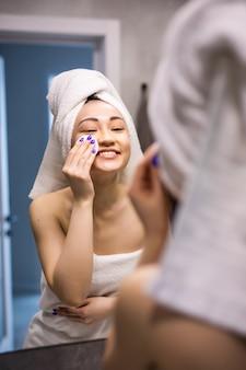 白いバスローブで美しいアジアの女性の素肌を洗って、朝の新鮮な日光の下で注意して顔をきれいにします