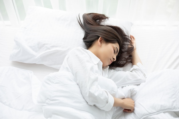 Beautiful asian woman basking and sleeping in white bed.