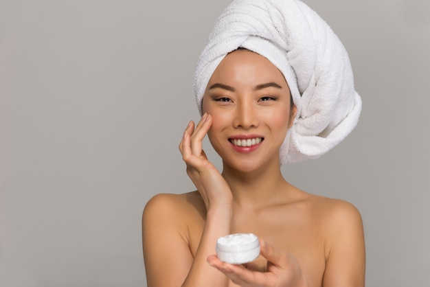 Красивые азиатские портреты красоты женщины. китайская девушка стоит перед зеркалом и заботится о ее взгляде. снимки студии красоты