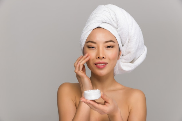 美しいアジアの女性の美しさの肖像画。鏡の前に立って彼女の顔の世話をしている中国の女の子。