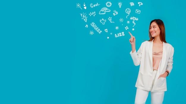 아름 다운 아시아 여자 블로거는 손으로 가리키고 자유형 낙서 및 장식 드로잉 그래픽으로 웃고 있습니다.