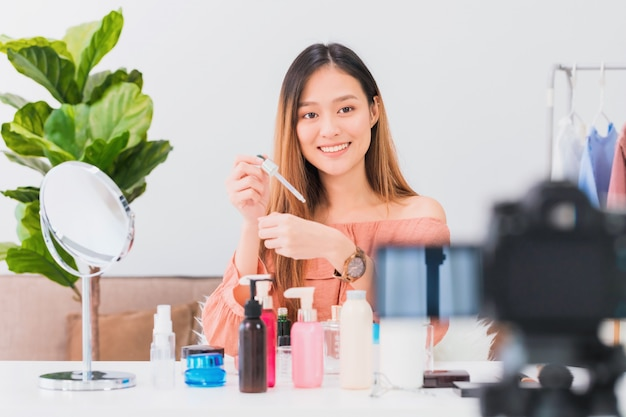 Beautiful asian woman blogger is showing how to make up and use cosmetics and recording vlog video at home.
