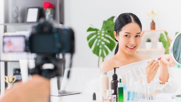 Блогер красивая азиатская женщина показывает, как составить и использовать косметику. перед зеркалом и камерой запись видеоблога в прямом эфире дома. концепция ухода за кожей для здорового лица.