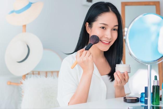 아름다운 아시아 여성 블로거가 화장품을 만들고 사용하는 방법을 보여주고 있습니다. 거울 앞에서 집에서 vlog 비디오 라이브 스트리밍을 녹화하는 스마트폰. 건강한 얼굴 개념을 위한 스킨케어.