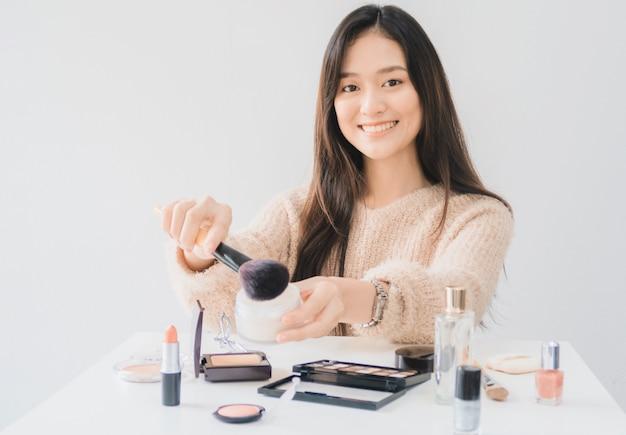 아름 다운 아시아 여자 블로거 화장품을 만들고 사용하는 방법을 보여줍니다.
