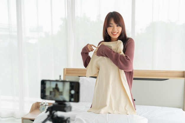 Beautiful asian woman blogger showing clothes on camera to recording vlog video live streaming at her shop