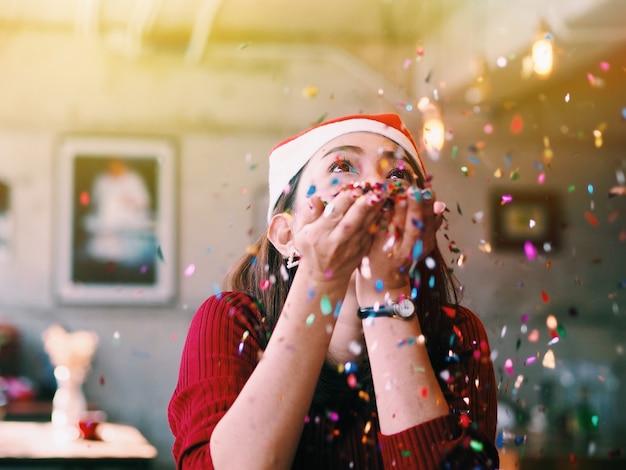 美しいアジアの女性が光っている紙吹雪を吹き飛ばします。クリスマスパーティーコンセプト。