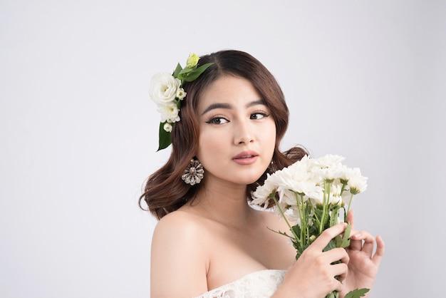 회색 배경에 아름 다운 아시아 여자 신부입니다. 전문 메이크업으로 클로즈업 초상화