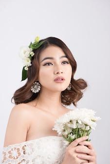 Красивая азиатская невеста женщины на серой предпосылке. портреты крупным планом с профессиональным макияжем