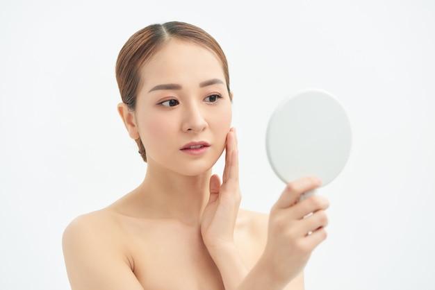 피부, 피부 관리, 여드름 치료를 확인하는 아름다운 아시아 여성. 스파 및 스킨케어 개념입니다.