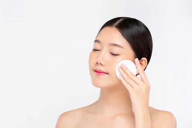 메이크업 리무버 패드로 얼굴을 청소하는 아름 다운 아시아 여자