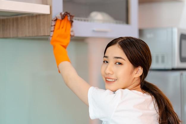 부엌 캐비닛을 청소하는 아름다운 아시아 여성