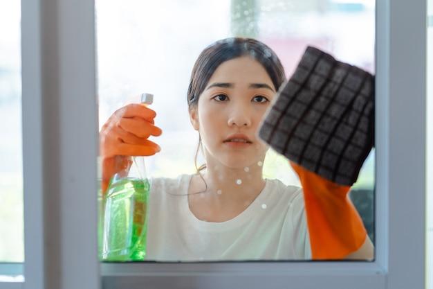 침실 유리문을 청소하는 아름다운 아시아 여성