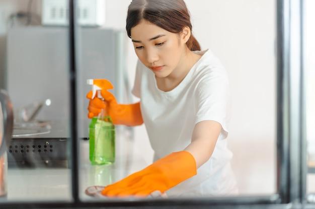부엌 영역을 청소하는 아름 다운 아시아 여자