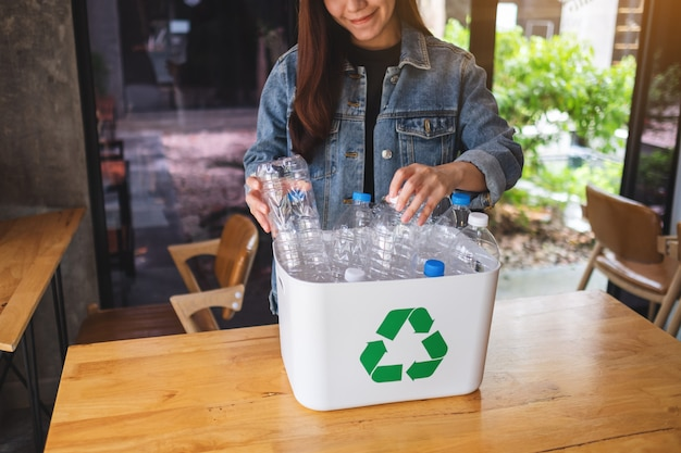 A beautiful asian woman collecting and separating recyclable garbage plastic bottles into a trash bin at home