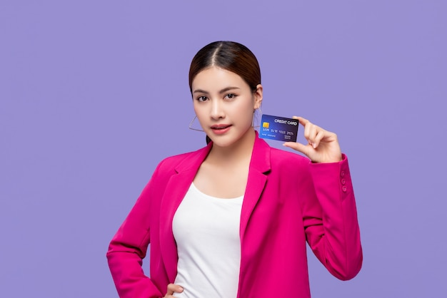 Beautiful asian woman in colorful pink suit showing credit card in hand