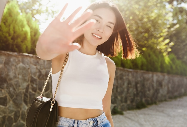Beautiful asian woman covering herself from camera and smiling, posing in trendy outfit, walking in park