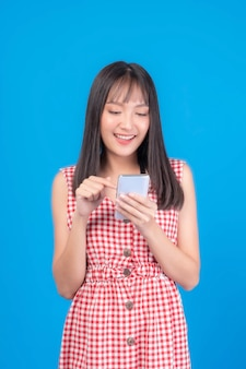 Beautiful asian woman cute girl bangs hair style in red dress playing a smart phone isolated on blue background - mobile phone uses a online banking for pay online shopping