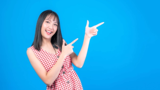 Beautiful asian woman cute girl with bangs hair style in blue t shirt smiling and pointing finger to empty copy space for present product or blank space for advertising isolated on blue background
