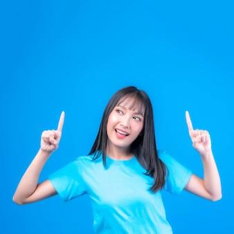 Красивая азиатская женщина милая девушка с челкой прически в синей футболке улыбается и показывает пальцем на пустое место для копирования настоящего продукта или пустое пространство для рекламы, изолированное на синем фоне