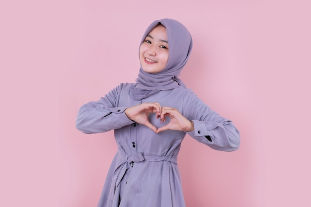 Beautiful asian woman doing a heart with her hands