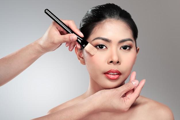 Beautiful asian woman doing makeup