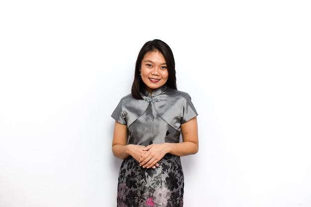 Красивая азиатская женщина в традиционном платье cheongsam делает позу, улыбаясь и глядя в камеру