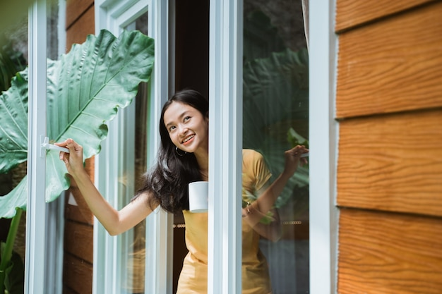 Красивая азиатская женщина пьет кофе утром у окна
