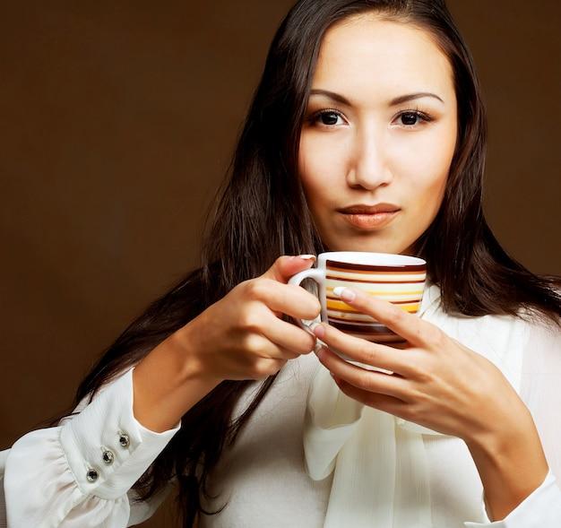 コーヒーやお茶を飲む美しいアジアの女性