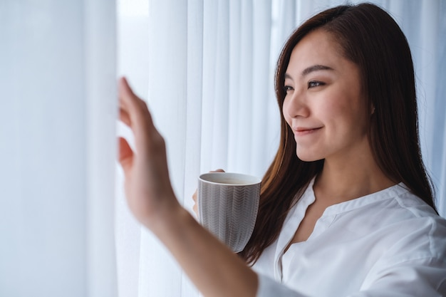 A beautiful asian woman drinking hot coffee while looking outside the window in the morning