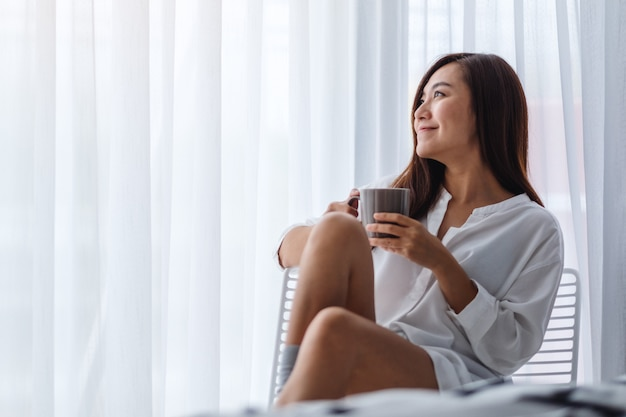 Premium Photo | A beautiful asian woman drinking hot coffee in a white  bedroom at home in the morning